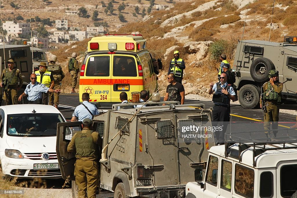 Israeli police and security forces gather at the scene where an Israeli died and three of his relatives were wounded after a suspected Palestinian gunman opened fire at their car on July 1, 2016 on route 60, near the al-Fawar refugee camp, south of Hebron in the occupied West Bank. The army said troops were 'searching the area for the gunman who fled the scene'. BADER