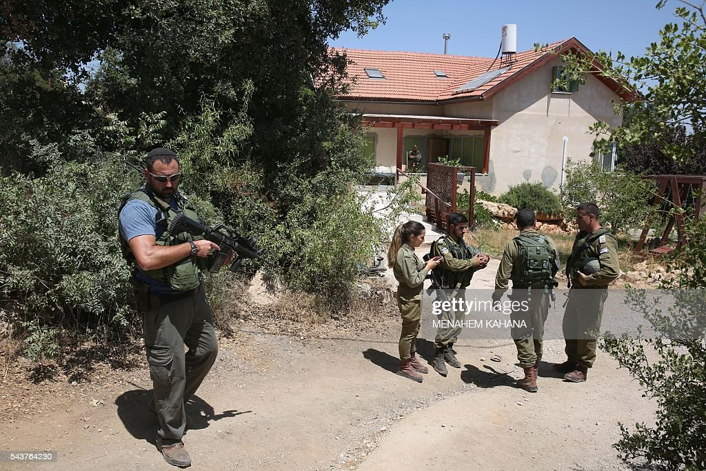 Israeli police and soldiers stand guard outside a house in the Jewish settlement of Kiryat Arba in the occupied West Bank where a 13-year-old Israeli girl was fatally stabbed in her bedroom on June 30, 2016. A Palestinian attacker stabbed a 13-year-old girl to death at her home in the Jewish settlement outside the city of Hebron before being shot dead by security guards, the Israeli army said. KAHANA