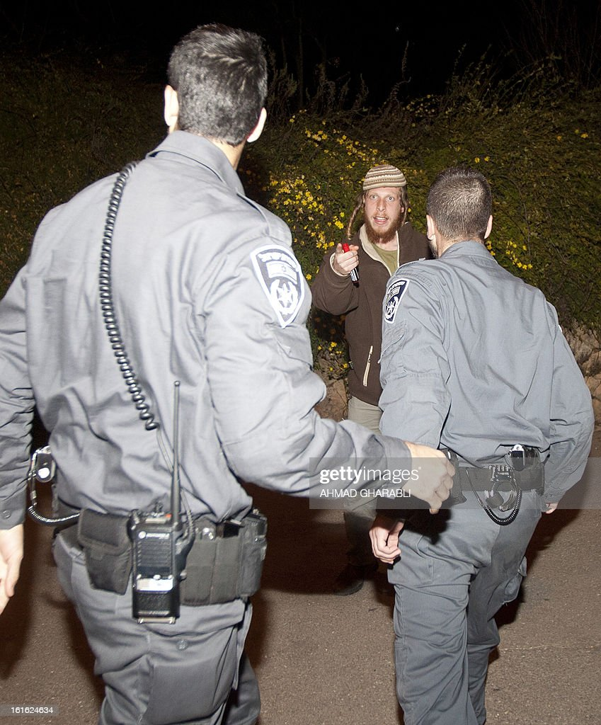 Israeli police confront an Israeli protesting outside the Israeli parliament or Knesset in Jerusalem on February 13, 2013. Israeli authorities demolished several buildings at a wildcat settlement outpost in the southern West Bank but the Supreme Court later issued a temporary injunction barring further demolition or eviction of settlers until further notice. Israel differentiates between 'legal' settlements and 'illegal' outposts set up without government permission, but the international community views all settlement activity on occupied territory as a violation of international law.