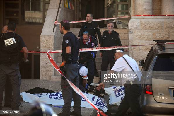 Israeli police crime scene investigators stand near bodies of suspected attackers outside a synagogue on November 18 2014 in Jerusalem Israel Four...
