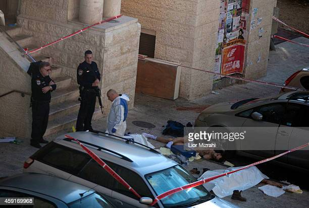 Israeli police crime scene investigators walk near bodies of suspected attackers outside a synagogue on November 18 2014 in Jerusalem Israel Four...