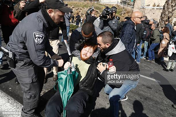 TOPSHOT Israeli police detain a demonstrator during a protest outside the defence ministry in Tel Aviv on January 4 in support of Israeli soldier...