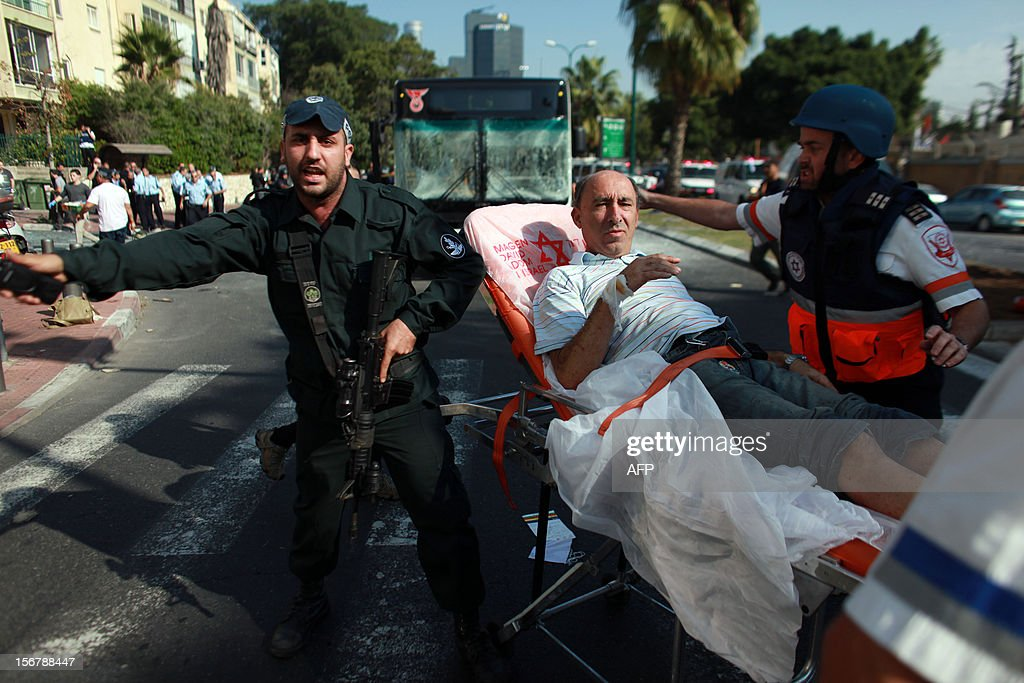 Israeli police evacuate wounded people after a blast ripped through a bus near the defence ministry in Tel Aviv on November 21, 2012. At least 10 people were injured in an explosion on a bus, Israel's emergency services said, in what an official said was 'a terrorist attack.' AFP PHOTO / DANIEL BAR-ON ===ISRAEL OUT== MAGAZINE OUT==