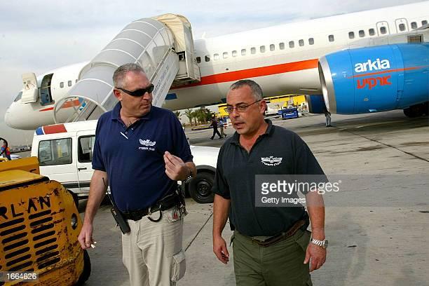 Israeli police explosive experts walk away from an Arkia Airlines passenger jet that landed safely November 28 2002 at Ben Gurion Airport in Tel Aviv...