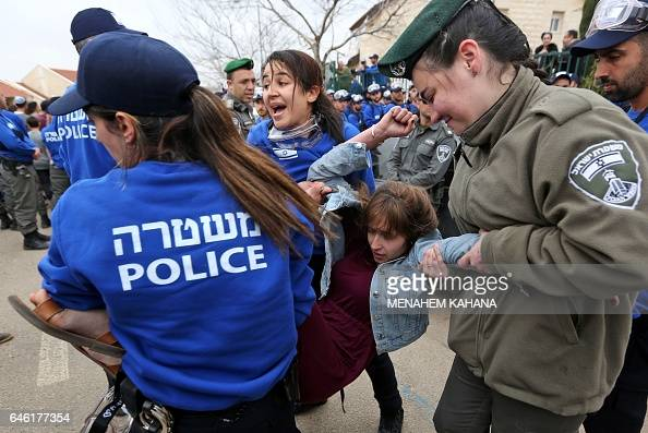 Israeli police forces carry away an Israeli supporter of settlements on February 28 2017 in the settlement of Ofra in the occupied West Bank during...