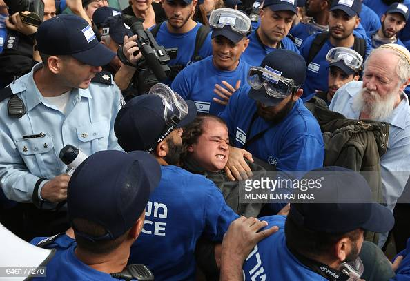TOPSHOT Israeli police forces carry away an Israeli youth supporter of settlements on February 28 2017 in the settlement of Ofra in the occupied West...