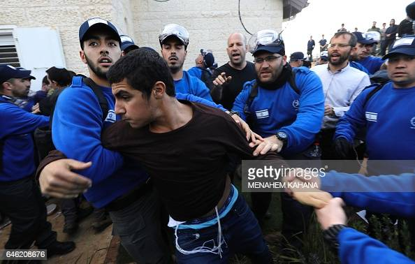 Israeli police forces carry away an Israeli youth supporter of settlements on February 28 2017 in the settlement of Ofra in the occupied West Bank...