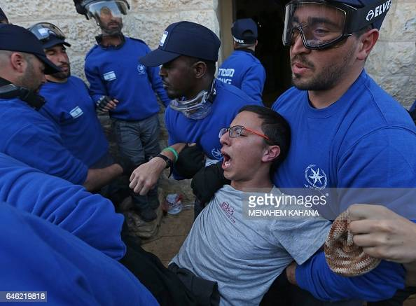 Israeli police forces evacuate Israeli supporters of settlements on February 28 2017 in the settlement of Ofra in the occupied West Bank during an...