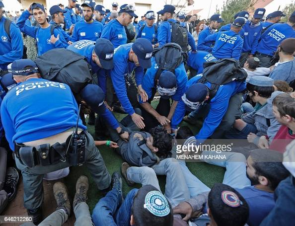 Israeli police forces evacuate Israeli youth supporters of settlements on February 28 2017 in the settlement of Ofra in the occupied West Bank during...