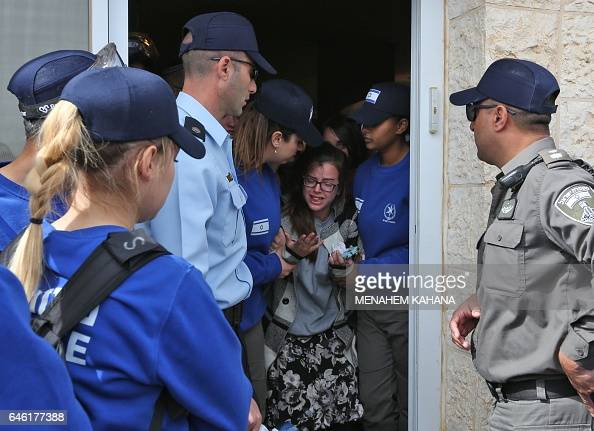 Israeli police forces move away an Israeli supporter of settlements on February 28 2017 in the settlement of Ofra in the occupied West Bank during an...