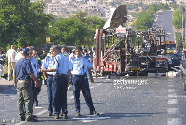 Israeli police inspect the scene of a suicide attack on a bus on the southern outskirts of Jerusalem 18 June 2002 Fourteen people were killed in the...