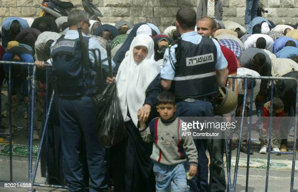 Israeli police let pass a woman and her son through security barriers at Lion's Gate into Jerusalem's Old City as Palestinian men carry out Friday...