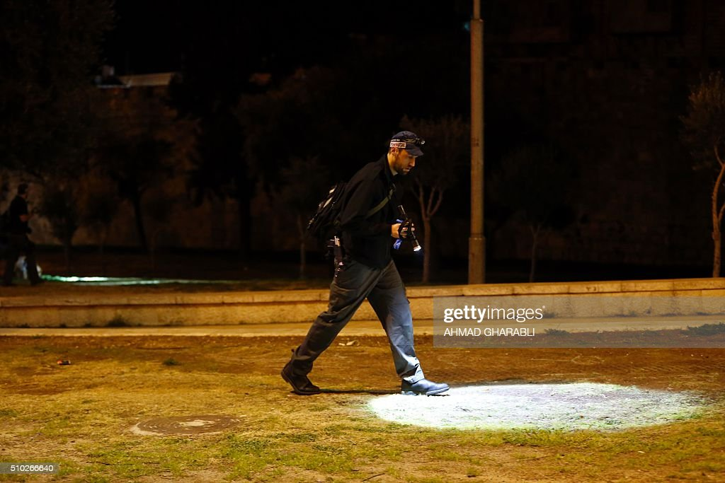 A Israeli police officer looks for evidences near the scene where a Palestinian man was shot dead by Israeli security after he opened fire towards Israeli security force near Damascus Gate, a main entrance to Jerusalem's Old City on February 14, 2016. A police statement described the attackers as firing 'improvised automatic weapons' but said no officers were harmed. / AFP / AHMAD GHARABLI