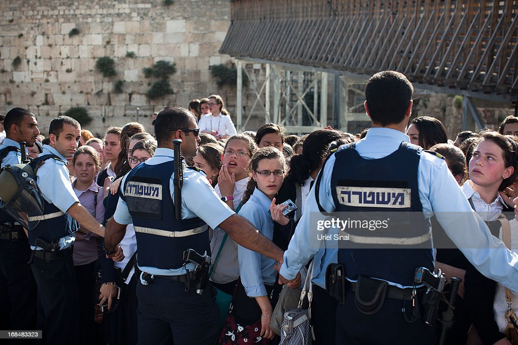 Israeli police officers block ultra-Orthodox protestors from reaching the religious group 'Women Of The Wall' while they hold a prayer service to mark the first day of the Jewish month of Sivan at the Western Wall on May 10, 2013 in Jerusalem, Israel. Thousands of ultra-Orthodox protestors clashed with Israeli police during the first monthly prayer service to be held by Women Of The Wall following the recent landmark ruling by Jerusalem District Court allowing women to wear prayer shawls at the Western Wall.