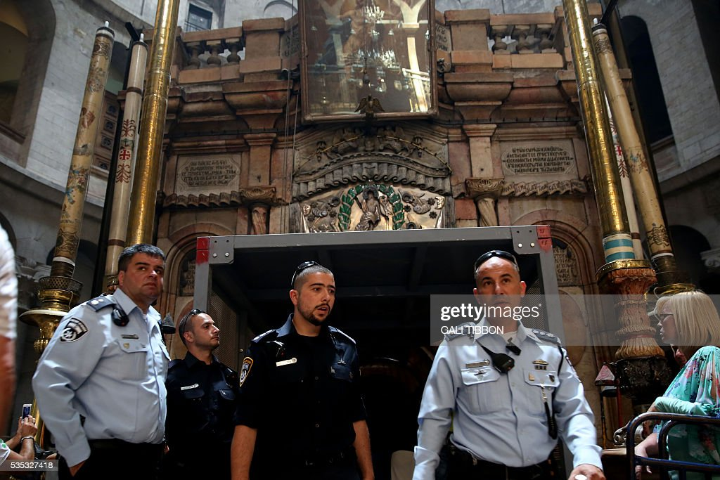 Israeli police officers come out of the Tomb of Jesus as they pass under a metal scaffolding built at the entrance ahead of the restoration on May 29, 2016, at the Church of the Holy Sepulchre in Jerusalem's Old City. The tomb where Jesus is said to have been buried before his resurrection, is to undergo major restoration. The restoration entrusted to a Greek team, is expected to be completed in early 2017 and the site will remain open to visitors in the meantime. / AFP / GALI