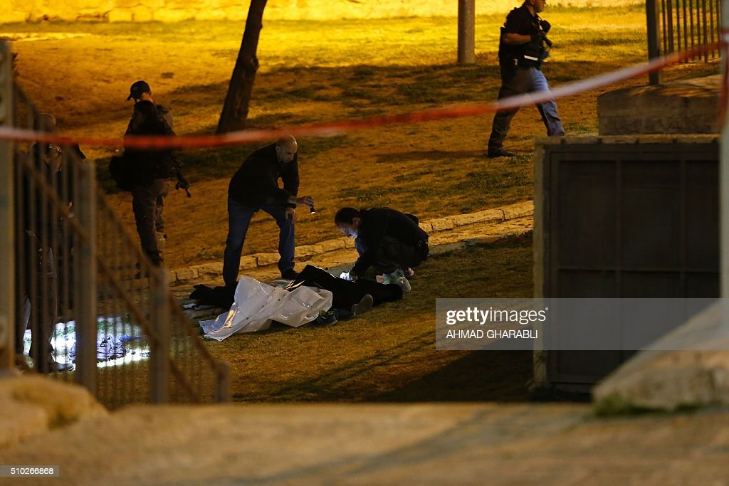 Israeli police officers look for evidences near the dead body of a Palestinian man who was shot by Israeli security after he opened fire towards Israeli security force near Damascus Gate, a main entrance to Jerusalem's Old City on February 14, 2016. A police statement described the attackers as firing 'improvised automatic weapons' but said no officers were harmed. / AFP / AHMAD GHARABLI