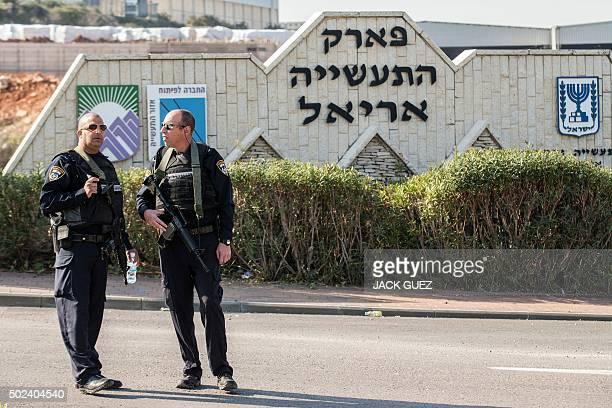 Israeli police officers stand guard at the scene where a Palestinian assailant was shot dead after he stabbed two Israeli security guards at an...