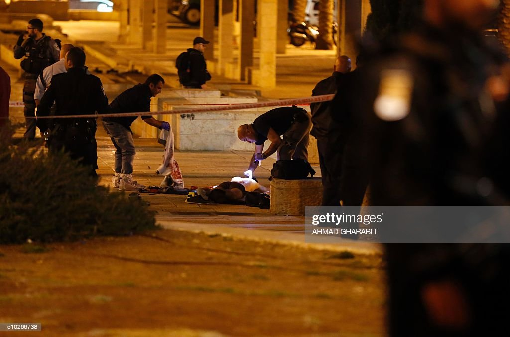 Israeli police officers stand near the body of a Palestinian man who was shot dead by Israeli security after he opened fire towards Israeli security force near Damascus Gate, a main entrance to Jerusalem's Old City on February 14, 2016. A police statement described the attackers as firing 'improvised automatic weapons' but said no officers were harmed. / AFP / AHMAD GHARABLI