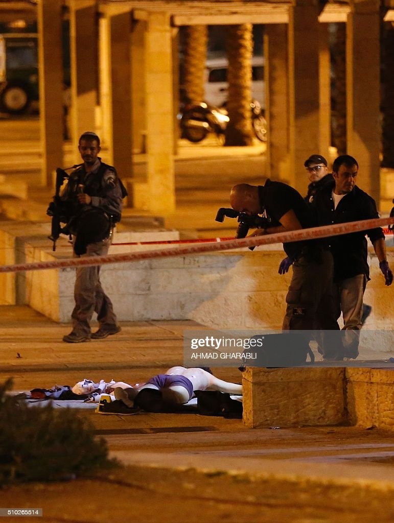Israeli police officers stand next to the dead body of a Palestinian man who was shot dead by Israeli security after he opened fire towards Israeli security force near Damascus Gate, a main entrance to Jerusalem's Old City on February 14, 2016. A police statement described the attackers as firing 'improvised automatic weapons' but said no officers were harmed. / AFP / AHMAD GHARABLI