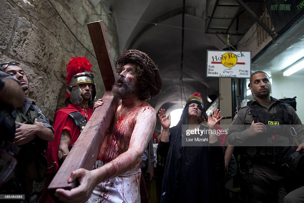 Israeli Police officers surround an Orthodox Christian pilgrim from 'The Hope of Glory' order as he re-enacts the Passion of Christ along the Via Dolorosa on April 18, 2014 in Jerusalem's old city, Israel.Thousands of Christian pilgrims from around the world have flocked to the Holy City to mark Good Friday and pray along the traditional route Jesus Christ took to his crucifixion, leading up to his resurrection on Easter.