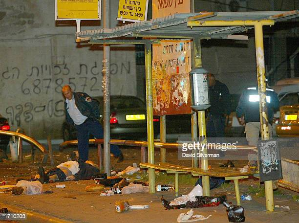 Israeli police officers walk near a body as they investigate the scene of one of two Palestinian suicide bombings January 5 2003 in Tel Aviv Israel...