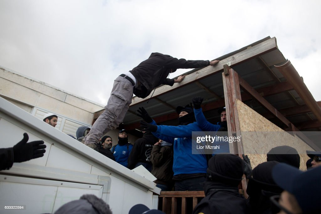 Israeli police scuffle with Israeli settlers as police take up positions in order to evacuate the settlers on February 1, 2017 in Amona, West Bank. Israeli Security forces have started evacuating residents from the illegal outpost of Amona in the West Bank on Wednesday, after hundreds of youths streamed into the outpost to fight the evacuation.