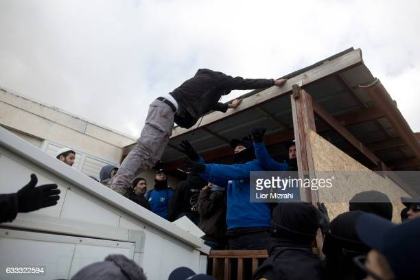 Israeli police scuffle with Israeli settlers as police take up positions in order to evacuate the settlers on February 1 2017 in Amona West Bank...
