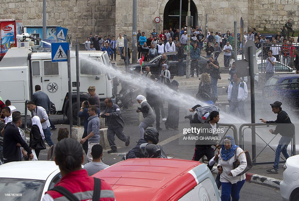 Israeli police spray water to disperse Palestinian protestors after clashes broke out outside Damascus gate in Jerusalem on May 15, 2013 during a rally to mark the 65th Nakba or 'catastrophe' of the Jewish state's creation in 1948, during which 760,000 Palestinians fled their homes. Thousands of Palestinians took to the streets in the West Bank and the Gaza Strip to demonstrate on Nakba Day and assert their 'right to return' to where their ancestors fled after the Israeli victory over Arab armies. AFP PHOTO/AHMAD GHARABLI