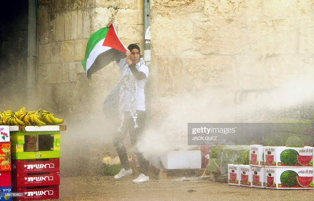 Israeli police spray water towards a Palestinian protestor holding her national flag after clashes broke out outside Damascus gate in Jerusalem on May 15, 2013 during a rally to mark the 65th Nakba or 'catastrophe' of the Jewish state's creation in 1948, during which 760,000 Palestinians fled their homes. Thousands of Palestinians took to the streets in the West Bank and the Gaza Strip to demonstrate on Nakba Day and assert their 'right to return' to where their ancestors fled after the Israeli victory over Arab armies.