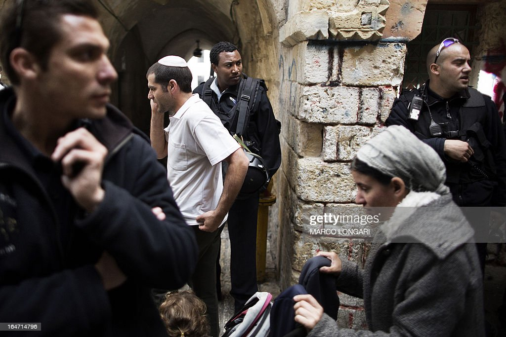 Israeli police stand guard as Israeli Jews leave the Temple Mount, known to the Palestinians as the al-Aqsa compound, in Jerusalem on March 27, 2013. Israeli police stopped far-right member of parliament, Moshe Feiglin, from entering the flashpoint holy site in Jerusalem fearing a violent response from Muslims at the site. AFP PHOTO/MARCO LONGARI