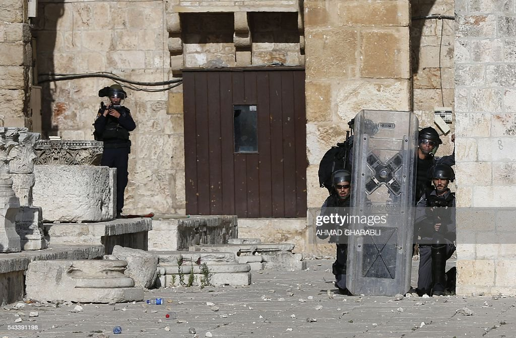 Israeli police take cover as Palestinian protesters throw stones at them at Jerusalem's Al-Aqsa mosque compound during clashes between Israeli police and Muslims for the thrid consecutive day on June 28, 2016 in Jerusalem's Old City. Israeli authorities announced they were closing Jerusalem's flashpoint Al-Aqsa mosque compound to non-Muslim visitors after a series of clashes between worshippers and police. The decision will apply until the end of the Muslim holy month of Ramadan next week. / AFP / AHMAD
