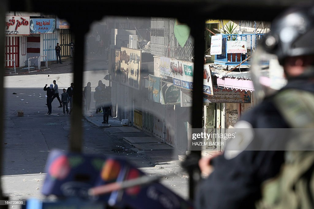 Israeli police takes cover during clashes with Palestinian protesters as security checks increase during the visit of Israeli Jews to the tomb of Othniel Ben Kenaz, considered holy by the Jewish faith, in the Palestinian side of the city of Hebron, on March 27, 2013. Religious Jews worldwide eat matzoth during the eight-day Pesach holiday that commemorates the Israelis' exodus from Egypt some 3,500 years ago and their ancestors' plight by refraining from eating leavened food products.