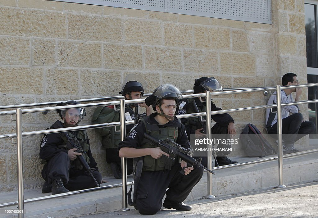 Israeli policemen and a civilian take cover as air raid sirens sound around Jerusalem on November 20, 2012. A rocket struck just south of Jerusalem as UN chief Ban Ki-moon was to arrive for talks on ending the Gaza crisis, AFP correspondents said. AFP PHOTO/AHMAD GHARABLI