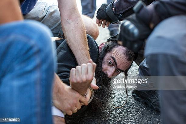 Israeli Policemen arrest an ultraOrthodox Jewish man suspected of stabbing participants of the Gay Pride Parade on July 30 2015 in Jerusalem Israel...