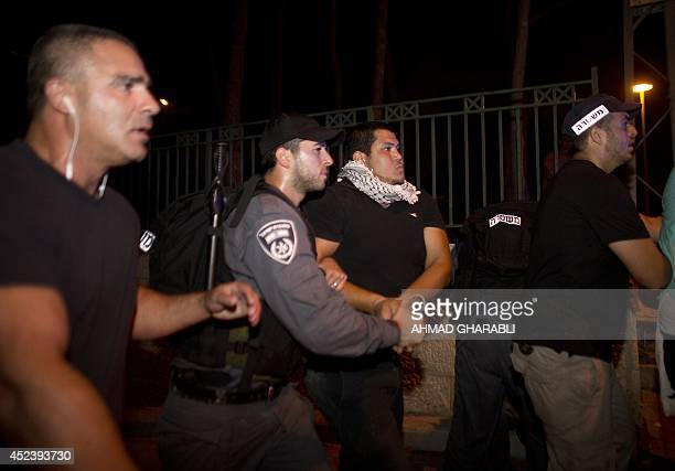 Israeli policemen arrest Israeli Arabs as they protest against the Israeli offensive on the Gaza Strip in the northern Israeli city of Haifa on July...