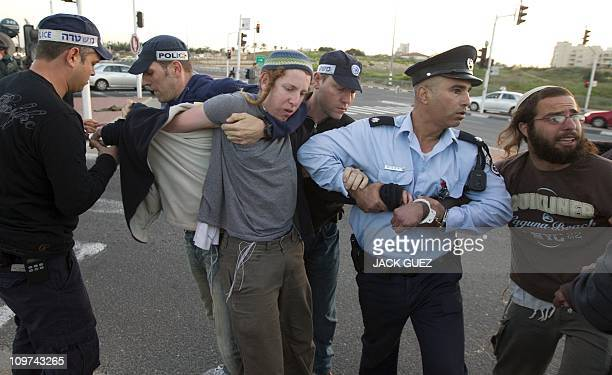 Israeli policemen briefly detain two Israeli settlers who were with other protesters blocking a main road at the entrance of Modi'In on March 03 2011...