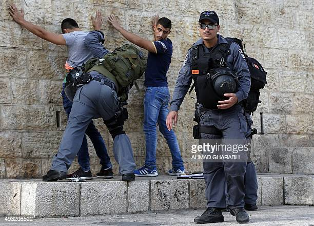 Israeli policemen check Palestinian youths at Damascus Gate in the Old City of Jerusalem on October 18 2015 as security measures are increased Israel...