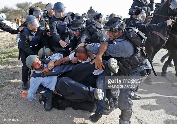TOPSHOT Israeli policemen detain a Bedouin man during clashes that followed a protest against home demolitions on January 18 2017 in the Bedouin...