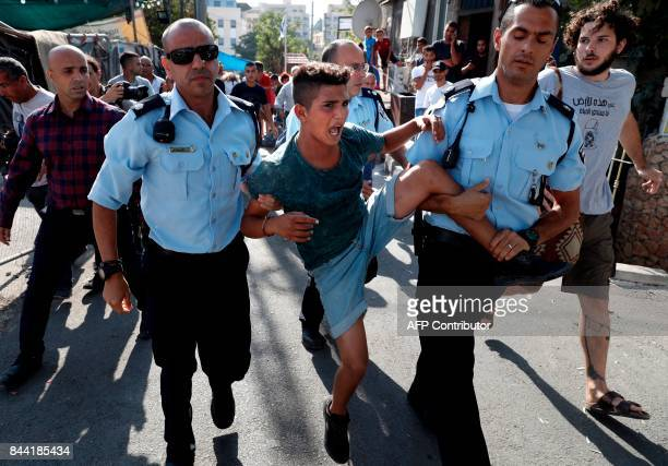 TOPSHOT Israeli policemen detain a Palestinian boy during a protest on September 8 2017 in front of a Palestinian house whose occupants were forcibly...