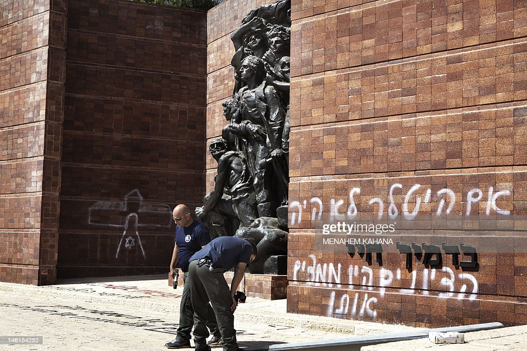 Israeli policemen inspect anti-Zionist Hebrew graffiti some thanking Hitler for the Holocaust and denouncing Zionism was sprayed at Jerusalem's Yad Vashem Holocaust museum compound June 11, 2012 in Jerusalem, with suspicion falling on ultra-Orthodox opponents of the state of Israel. Several slogans were sprayed on the red-brick Wall of Remembrance in Warsaw Ghetto Square, one of which read: 'The Zionist leadership wanted the Holocaust,' while the other reads, 'If Hitler hadn't existed, the Zionists would have invented him.'