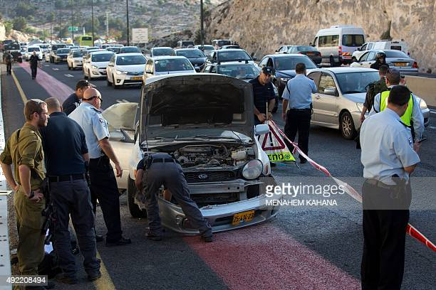 Israeli policemen inspect the damaged car of a Palestinian woman after she detonated a small bomb on October 11 2015 on the highway leading from the...