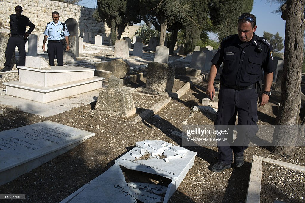 Israeli policemen inspect vandalized tombstones at a Christian cemetery located in mount Zion, outside Jerusalem's Old City on September 29, 2013. Police caught four young Israelis red-handed as they vandalized 15 Christian tombstones in the graveyard near the Old City of the holy city.