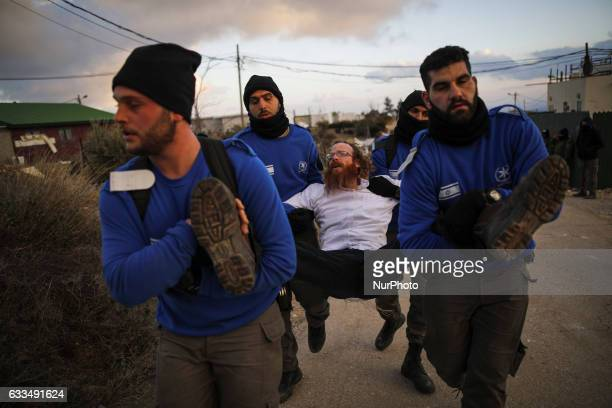 Israeli policemen remove an ultra orthodox prosettlement activist during an operation by Israeli forces to evict settlers from the illegal settlement...