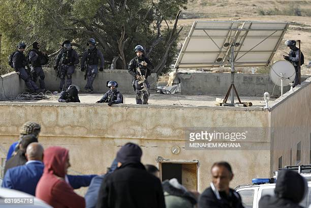 Israeli policemen take aim as they hold a position atop a building in the Bedouin village of Umm alHiran which is not recognized by the Israeli...