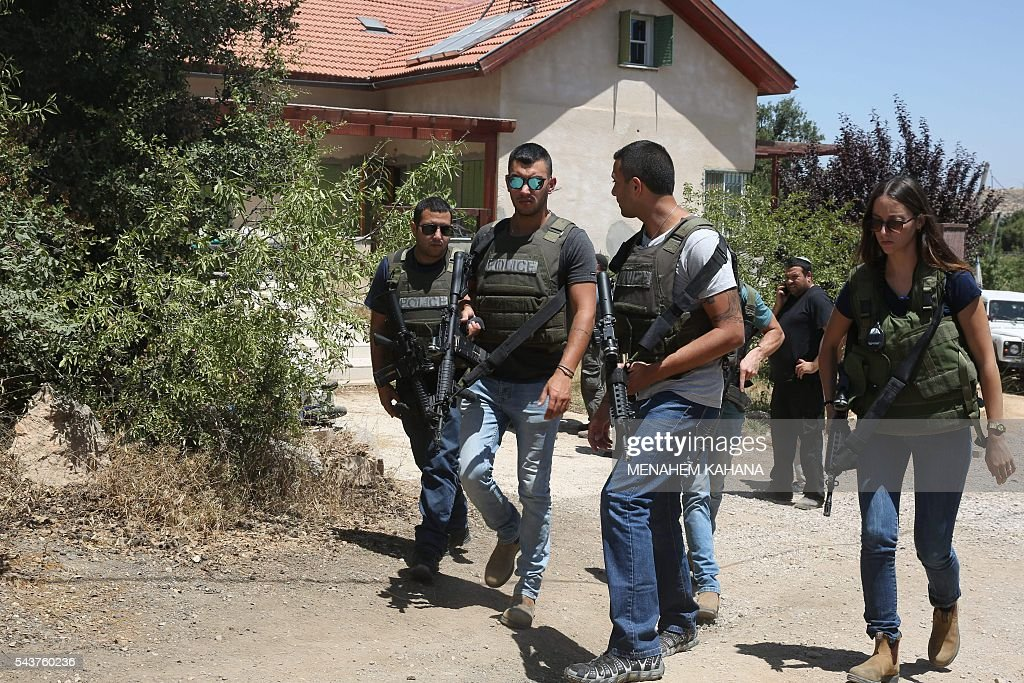 Israeli policemen walk outside a house in the Jewish settlement of Kiryat Arba in the occupied West Bank where a 13-year-old Israeli girl was fatally stabbed in her bedroom on June 30, 2016. A Palestinian attacker stabbed a 13-year-old girl to death at her home in the Jewish settlement outside the city of Hebron before being shot dead by security guards, the Israeli army said. KAHANA