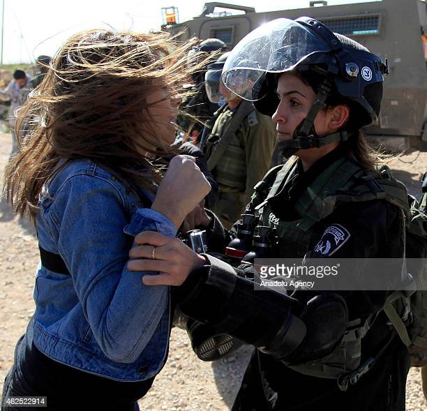 Israeli policewoman argues with a Palestinian protestor on January 30 2015 in Bilin west of Ramallah during a march to protest against West Bank...