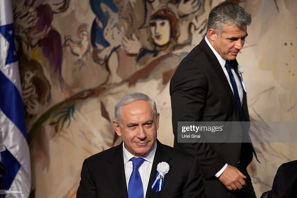 Israeli politician <a gi-track='captionPersonalityLinkClicked' href=/galleries/search?phrase=Yair+Lapid&family=editorial&specificpeople=5366792 ng-click='$event.stopPropagation()'>Yair Lapid</a> (C), leader of the Yesh Atid party, walks past Prime Minister <a gi-track='captionPersonalityLinkClicked' href=/galleries/search?phrase=Benjamin+Netanyahu&family=editorial&specificpeople=118594 ng-click='$event.stopPropagation()'>Benjamin Netanyahu</a> during a reception marking the opening of the 19th Knesset (Israeli parliament) on February 5, 2013 in Jerusalem, Israel. The 120 members of the Knesset included a record 48 new law makers.