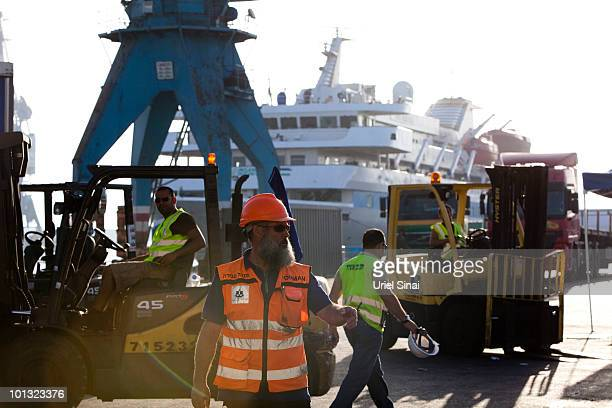 Israeli port workers prepare humanitarian aid seized from a peace flotilla to be sent to Gaza as the ship Mavi Marmara is seen in the back at the...
