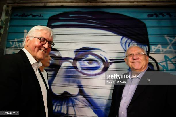 Israeli President Reuven Rivlin and his German counterpart FrankWalter Steinmeier stand next to a graffiti depicting Rivlin's greatgrandfather as...