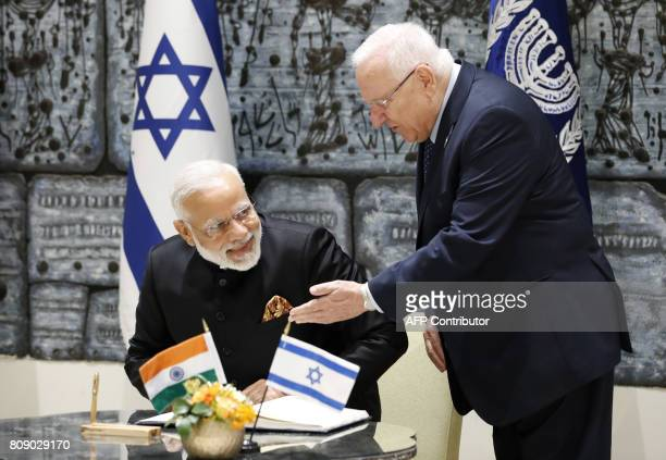 Israeli President Reuven Rivlin gestures as Indian Prime Minister Narendra Modi sits to sign the guest book during a welcome ceremony at the...